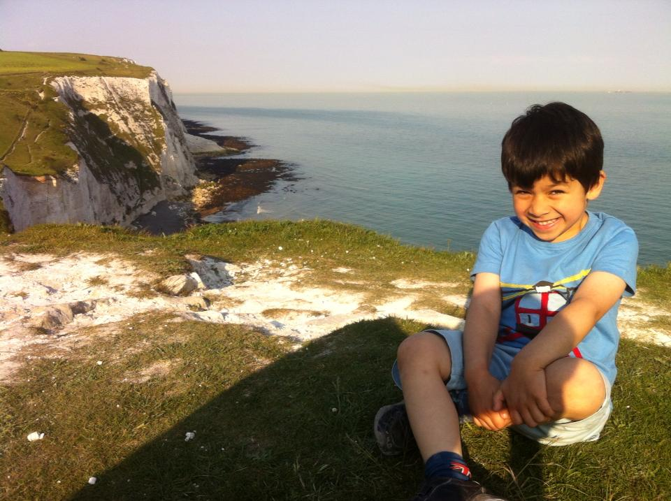 Boy sitting next to the white cliffs of dover
