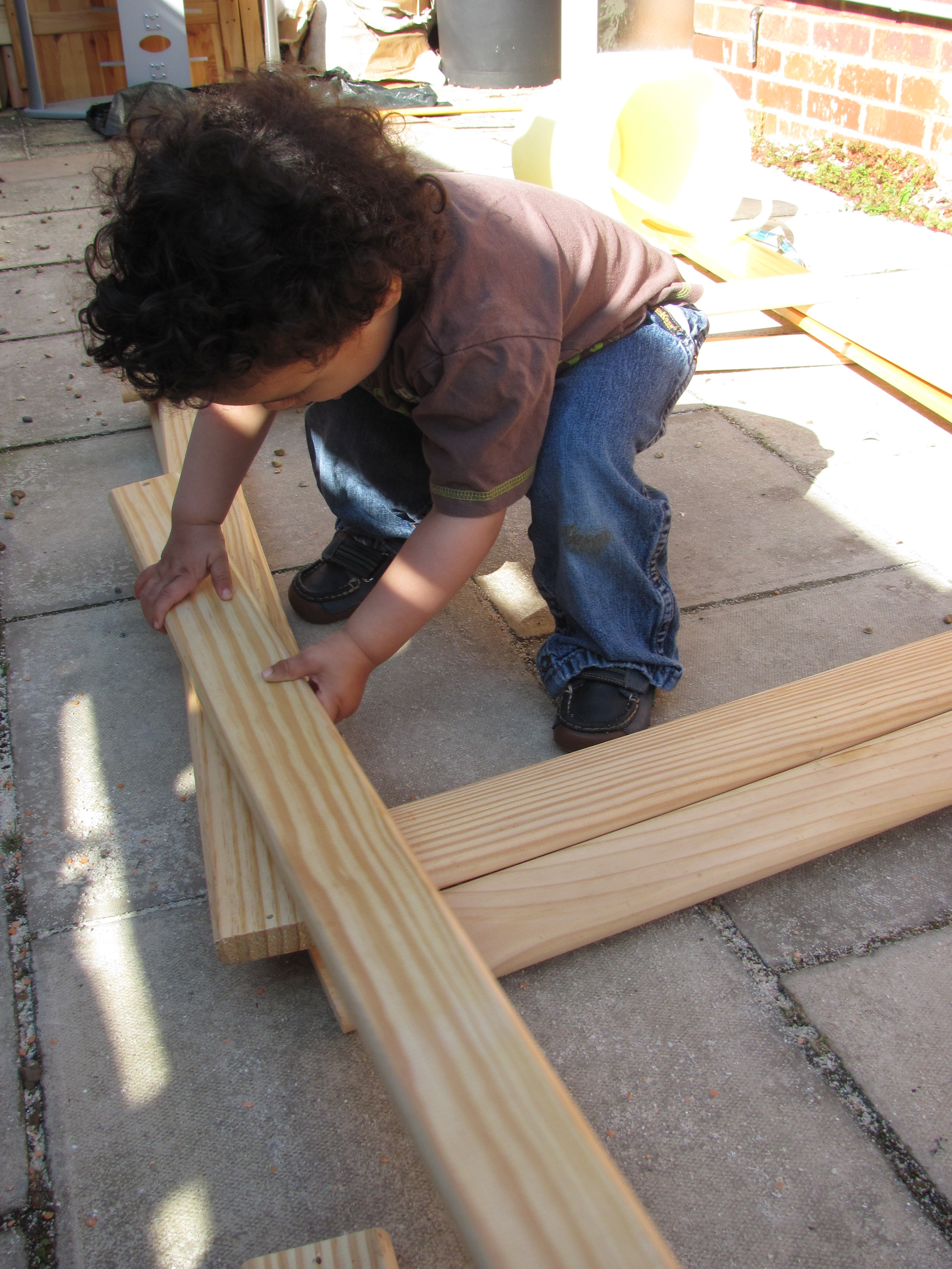 loose parts play - playing with wooden bed slats, building for large scale construction play