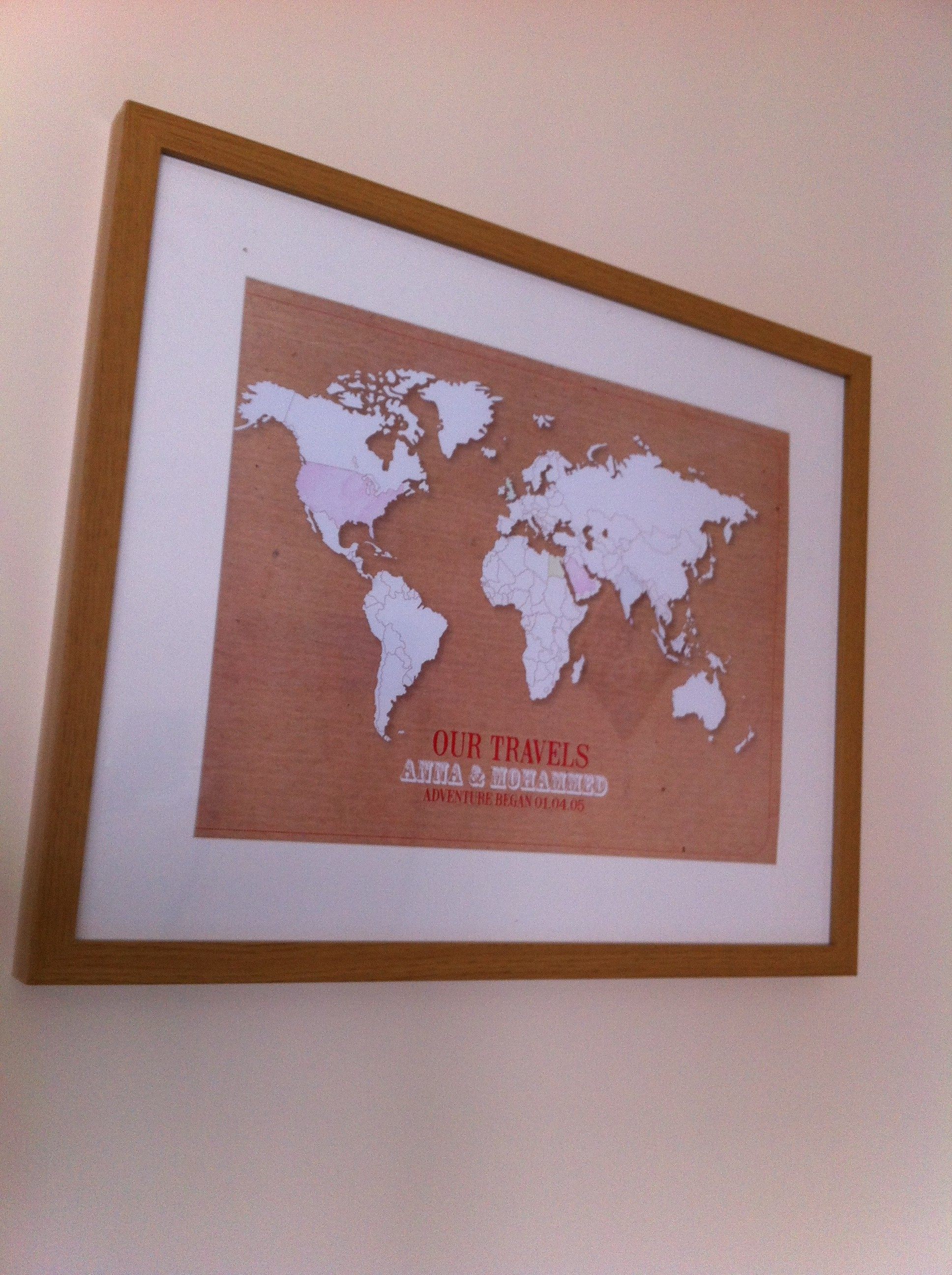 personalised world map on the wall in an oak frame