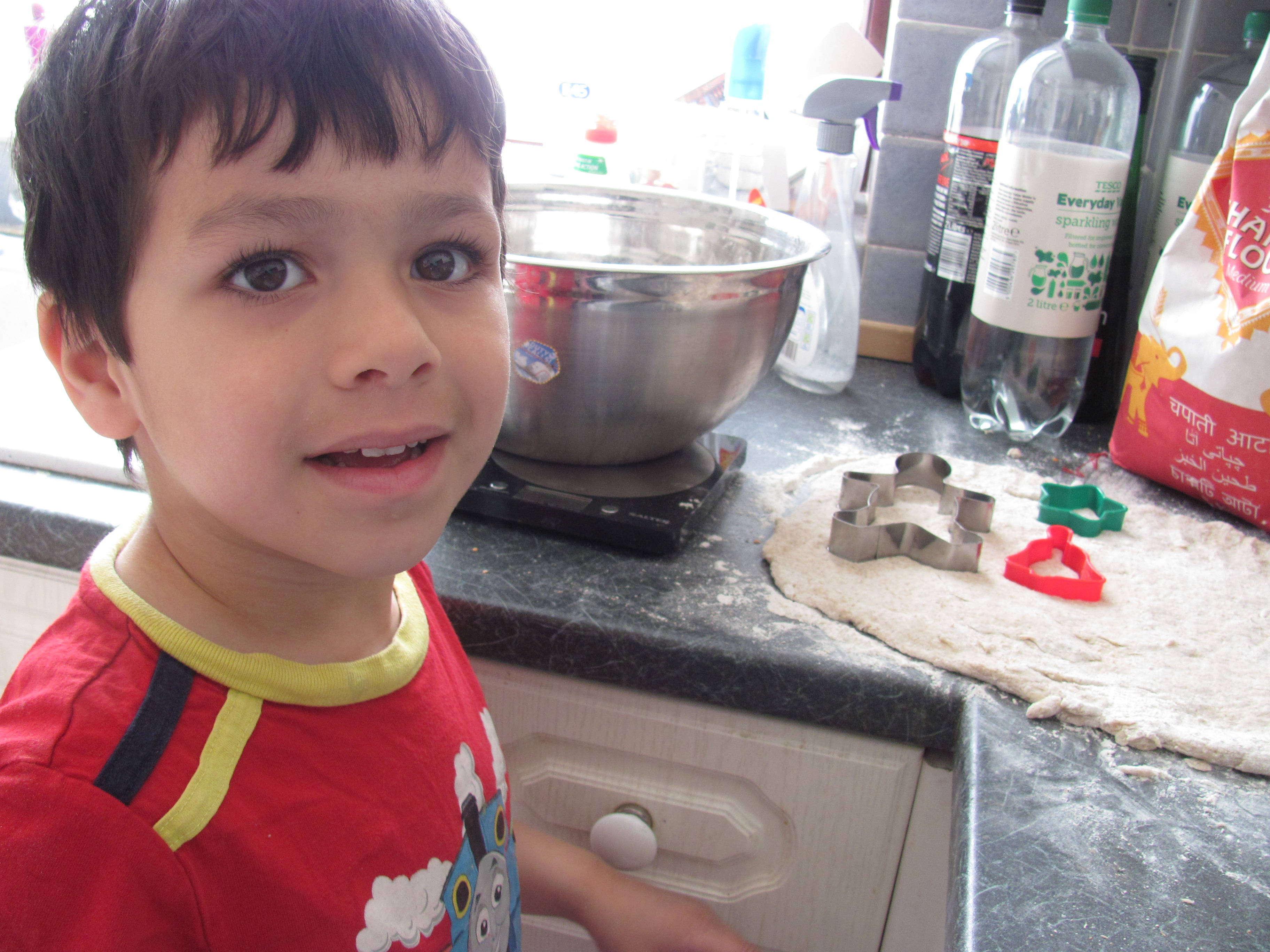 in the kitchen children making roti cutting out shapes from the dough