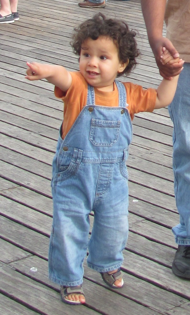 toddler boy in dungarees and orange tshirt, walking with his dad in brighton, enthusiastically pointing. toddler pointing in dungarees
