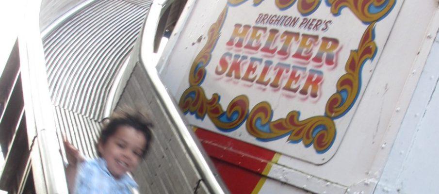 little boy coming down the helter skelter big slide in brighton, sack slide, fairground slide