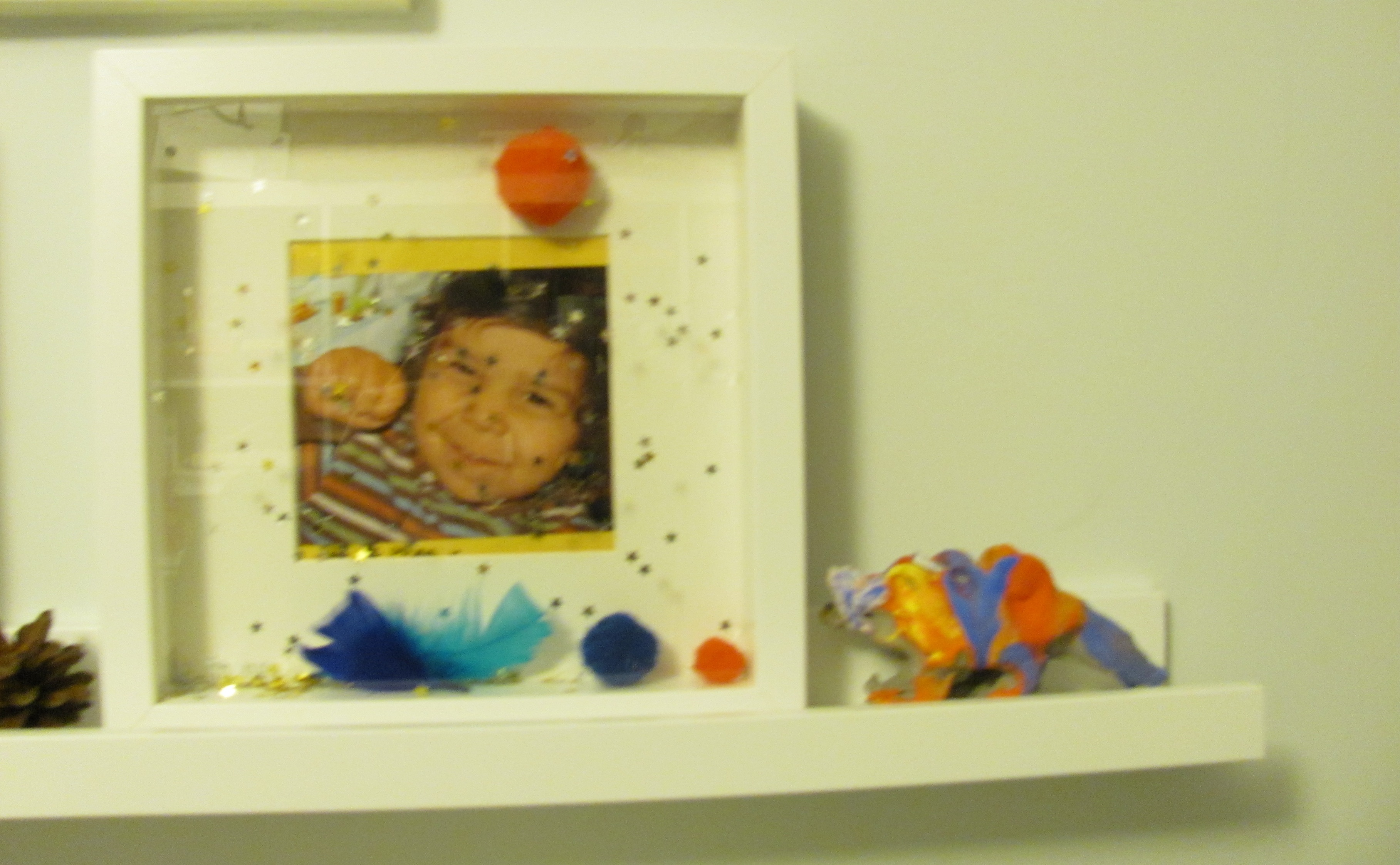 """picture of a boy in a frame signing """"yes"""" signalong makaton decorated frame and toy clay dinosaur"""