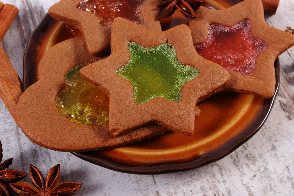 Stained glass gingerbread on old wooden background, christmas time